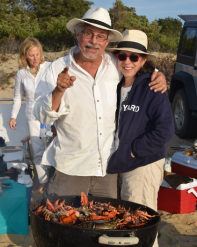 Steven and Barbara on beach with lobsters on grill